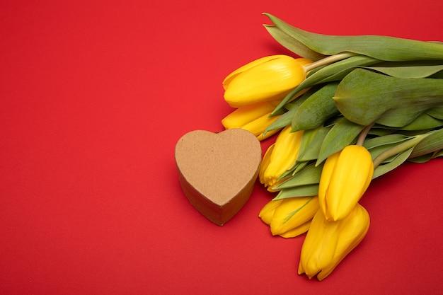 Koncepcja gratulacje z okazji dnia matki wakacje, walentynki. żółte tulipany i pudełko w kształcie serca wykonane z tektury rzemieślniczej na czerwonym tle. skopiuj miejsce, mock up. zamknij zdjęcie