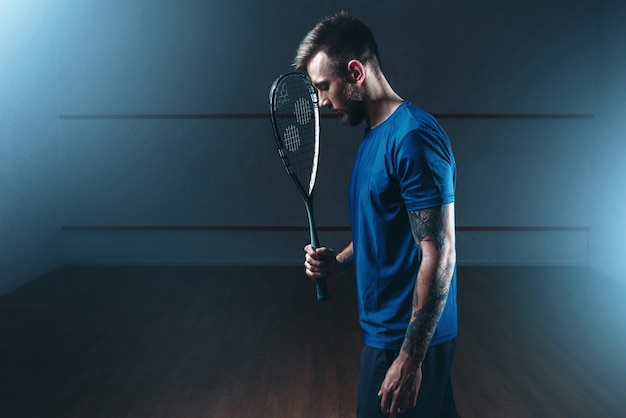 Koncepcja gry w squasha, męski gracz z rakietą