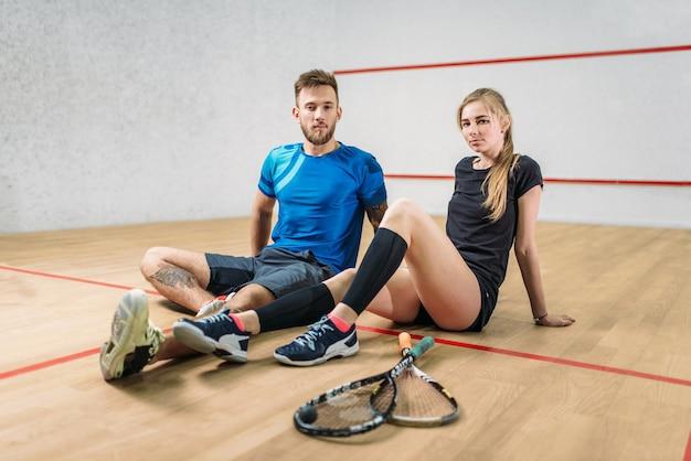 Koncepcja gry w squasha, młoda para, rakiety, piłka