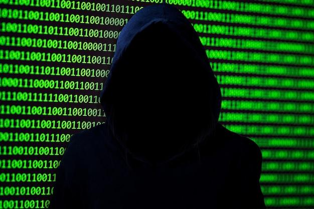 Koncepcja hakera. nierozpoznana osoba w kapturze łamie komputerowe kody binarne.