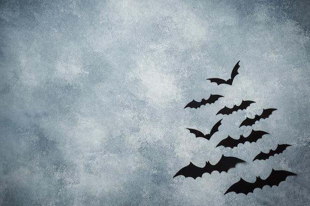 Koncepcja halloween. czarne papierowe nietoperze na szaro
