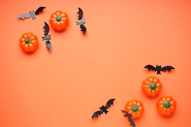 Koncepcja halloween. dynie halloween i nietoperze na pomarańczowym tle, miejsce na tekst, leżał płasko.