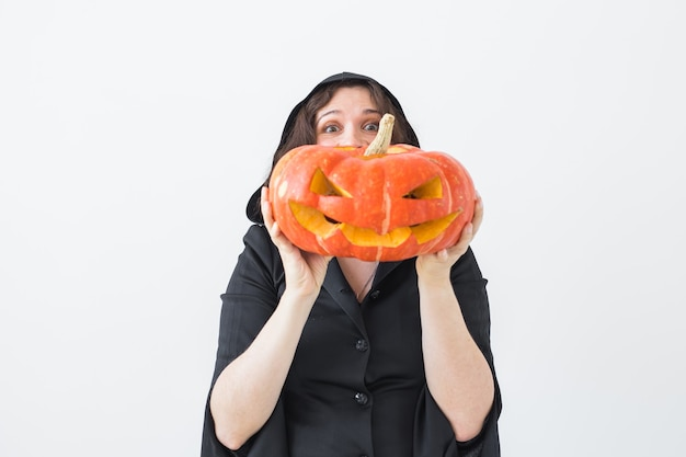 Koncepcja halloween i maskarady - piękna młoda kobieta pozuje z dyni jack-o'-lantern