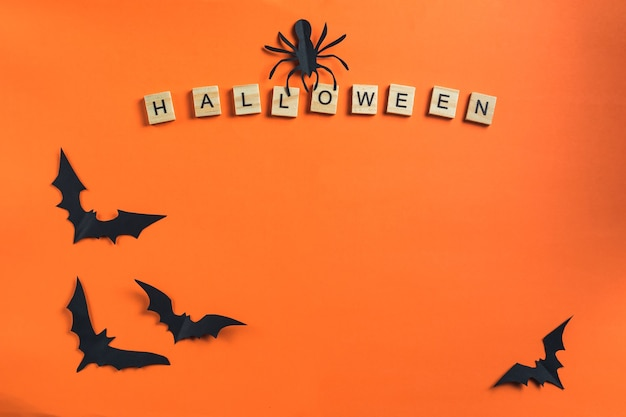 Koncepcja halloween i papierowe dekoracje. napis z drewnianych kostek i nietoperzy wyciętych z czarnego papieru na pomarańczowym tle. styl cięcia papieru. przestrzeń kopii w widoku z góry