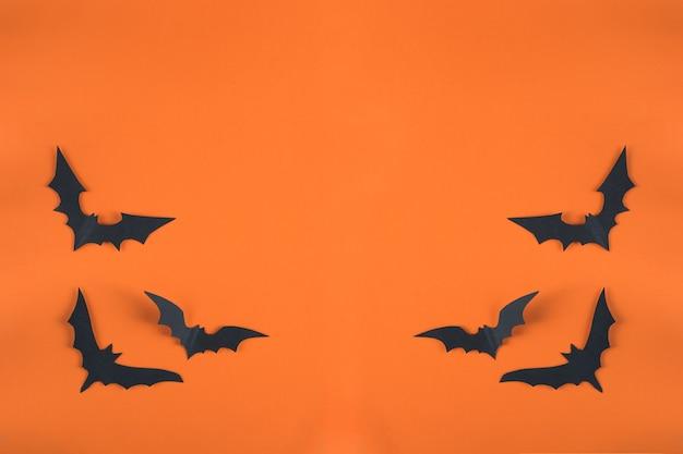 Koncepcja halloween i papierowe dekoracje. nietoperze wycięte z czarnego papieru na pomarańczowym tle. styl cięcia papieru. przestrzeń kopii w widoku z góry