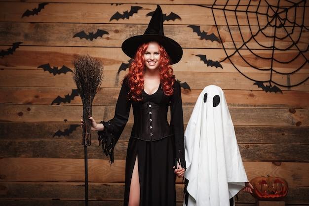 Koncepcja halloween - matka czarownica i mały biały duch robi cukierek albo psikus z okazji halloween pozowanie z zakrzywionymi dyniami nad nietoperzami i pajęczyną na drewnianym tle studio.