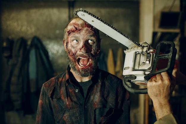 Koncepcja halloween obrony zombie i piłą łańcuchową. makijaż skóry i zakrwawionej twarzy