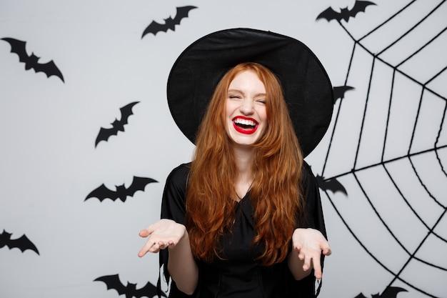 Koncepcja halloween - piękna czarownica trzymająca rękę i uśmiechająca się nad szarą ścianą.