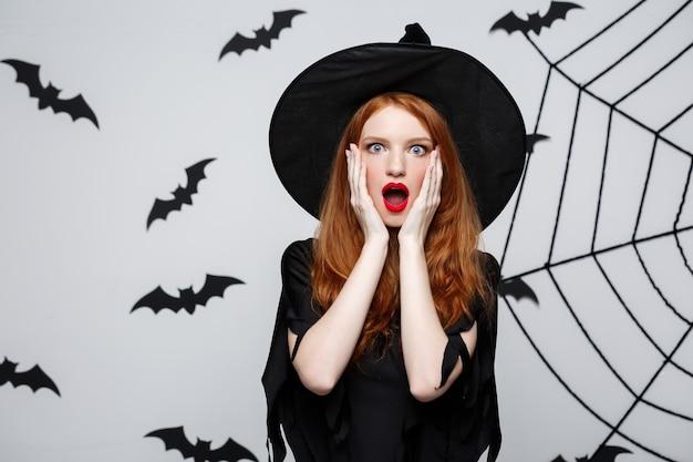 Koncepcja halloween - piękna kaukaska czarownica szokująca czymś na szarej ścianie.