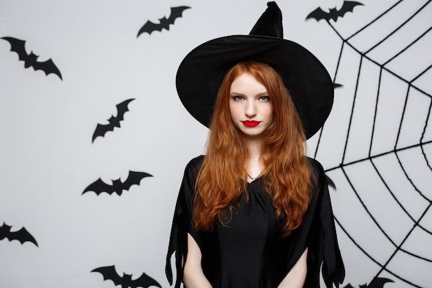 Koncepcja halloween - piękna poważna wiedźma z gniewnym wyrazem twarzy na szarej ścianie.