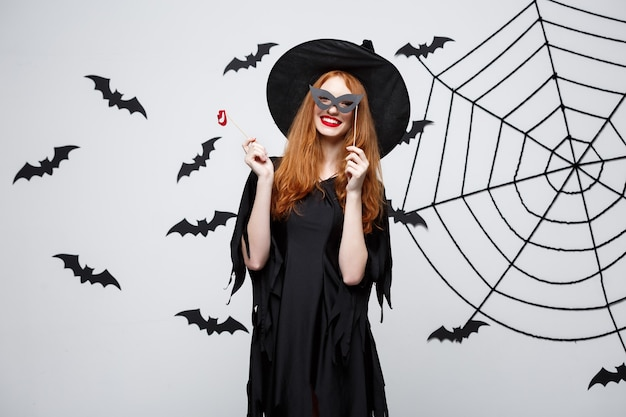 Koncepcja halloween - piękne dziewczyny w czarnych sukniach czarownic posiadających rekwizyty.