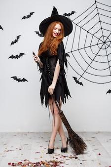 Koncepcja Halloween Szczęśliwa Elegancka Wiedźma Lubi Bawić Się Miotłą Imprezą Halloweenową Nad Szarą ścianą Darmowe Zdjęcia