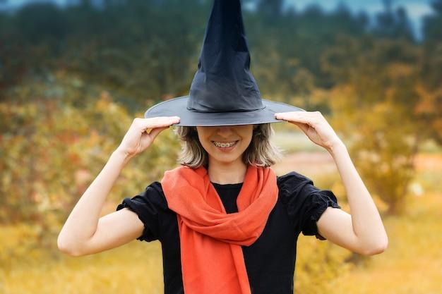 Koncepcja halloween uśmiechnięta młoda wiedźma w czarnym kapeluszu i pomarańczowym szaliku