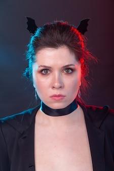 Koncepcja halloween, wakacji i karnawału - wampirzyca kobieta w kurtce iz uszami nietoperza w stylu gotyckim.