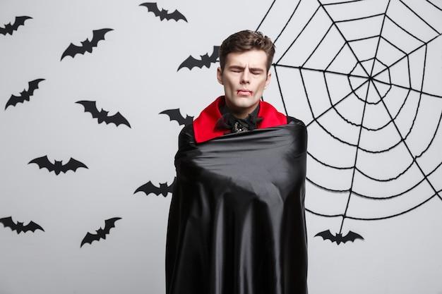 Koncepcja halloween wampira - portret przystojny wampir kaukaski w czarno-czerwonym kostiumie na halloween.