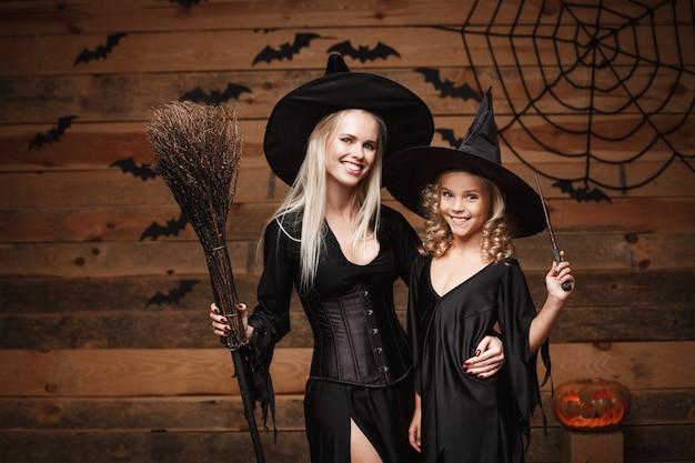 Koncepcja halloween - wesoła matka i jej córka w kostiumach czarownic świętują halloween z zakrzywionymi dyniami nad nietoperzami i pajęczyną na drewnianej ścianie.
