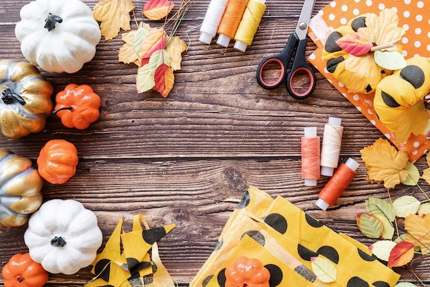 Koncepcja halloween. widok z góry na dekoracje na halloween i przedmioty do szycia, dzięki czemu tekstylne rękodzieło z dyni z miejsca na kopię na drewnianym tle