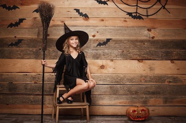 Koncepcja halloween witch - pełnometrażowe ujęcie małego dziecka rasy kaukaskiej czarownicy pozowanie z magiczną miotłą na tle nietoperza i pajęczyny.