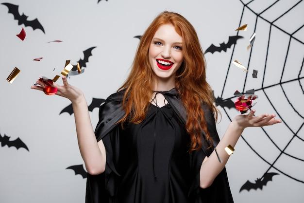 Koncepcja halloween witch - szczęśliwa elegancka wiedźma rzucająca konfetti na przyjęcie z okazji halloween nad ścianą nietoperza i pająka.