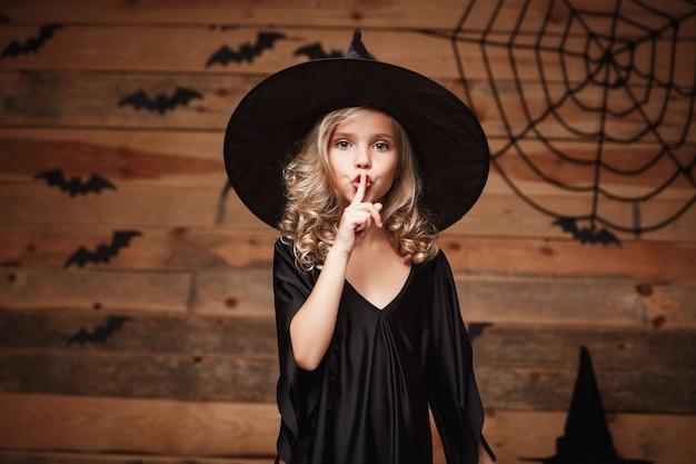 Koncepcja halloween witch - zbliżenie strzał małego dziecka kaukaskiej czarownicy trzyma palec wskazujący na ustach, prosząc o zachowanie ciszy.
