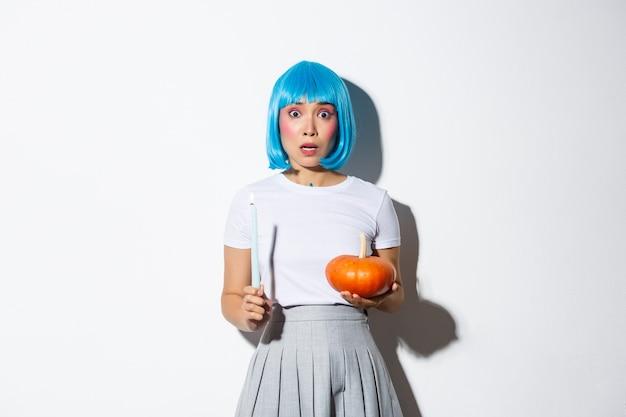 Koncepcja halloween. wizerunek przestraszonej azjatki w niebieskiej peruce wyglądającej na zdenerwowaną i przestraszoną, trzymającej świecę i dyni.