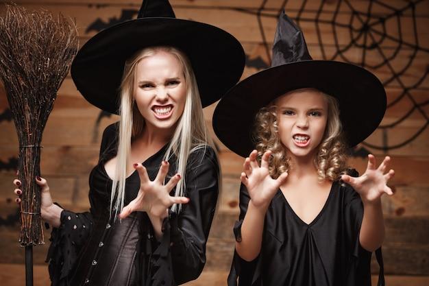 Koncepcja halloween - zbliżenie kaukaska matka i jej córka w kostiumach czarownic świętują halloween z zakrzywionymi dyniami nad nietoperzami i pajęczyną na drewnianej ścianie.