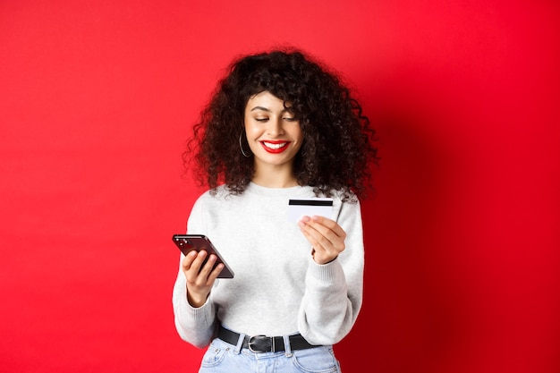 Koncepcja handlu elektronicznego i zakupów online. młoda nowoczesna kobieta płaci kartą kredytową, kupując smartfonem, stojąc na czerwonej ścianie.