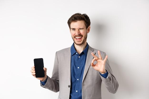 Koncepcja handlu elektronicznego i zakupów online. sukcesy biznesmen zarabia pieniądze na smartfonie, pokazując pusty ekran telefonu i znak w porządku, mrugając szczęśliwy na aparat.