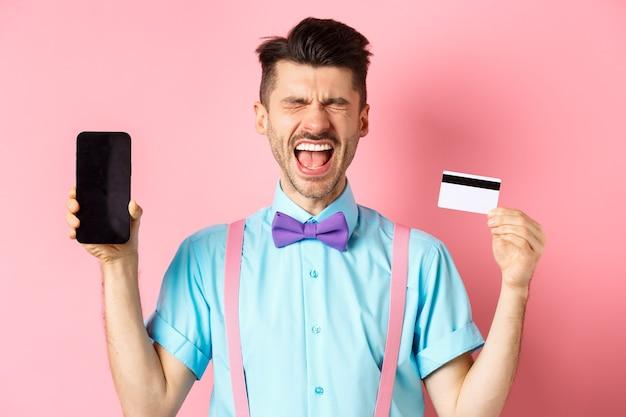 Koncepcja handlu elektronicznego i zakupów. płaczący mężczyzna pokazuje pusty ekran smartfona i plastikową kartę kredytową, czuje się sfrustrowany, stojąc na różowym tle.