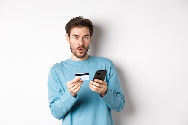 Koncepcja handlu elektronicznego i zakupów. podekscytowany mężczyzna wyglądający na rozbawionego podczas składania zamówienia online, trzymając plastikową kartę kredytową i smartfon, stojąc na białym tle.