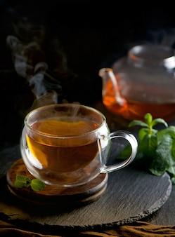 Koncepcja herbaty, imbryk z herbatą na powierzchni drewna, ceremonia parzenia herbaty, zielona herbata w przezroczystej filiżance