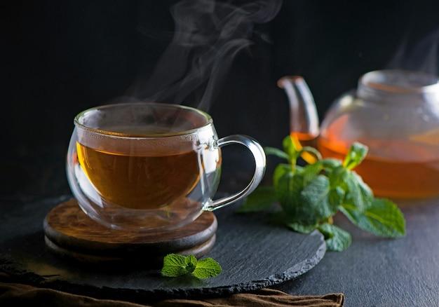 Koncepcja herbaty, imbryk z herbatą na tle drewna, ceremonia parzenia herbaty, zielona herbata w przezroczystej filiżance