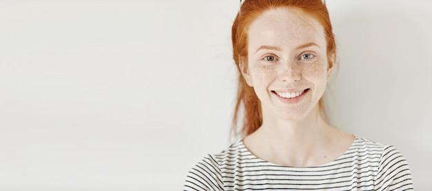 Koncepcja heterochromii. atrakcyjna młoda kobieta z rudymi włosami i różnymi kolorowymi oczami uśmiechając się radośnie, pozowanie na białym tle