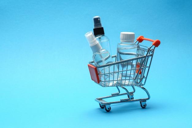 Koncepcja higieny ochrony przed wirusem koronowym - płyn odkażający do rąk alkohol w troplley koszyk na niebieskim tle. . prać ręcznie w koszu