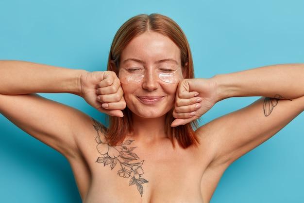 Koncepcja higieny osobistej i kosmetologii. zadowolona piegowata kobieta z naturalnymi rudymi włosami, trzyma dłonie w pięści przy twarzy, stoi nago na niebieskiej ścianie, nosi łaty pod oczami do podnoszenia