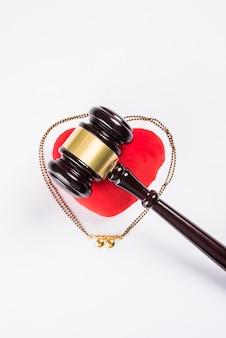 Koncepcja hinduskiego prawa małżeńskiego przedstawiająca drewniany młotek, mangalsutra i czerwone wypchane serce, selektywne skupienie