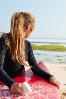 Koncepcja hobby i wakacji. plenerowe ujęcie jasnowłosego surferki ubranego w czarny kombinezon z kawałkiem wosku do surfingu