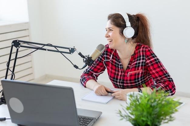 Koncepcja hosta radia - radosna kobieta ubrana w koszulę w kratę pracująca w radiu