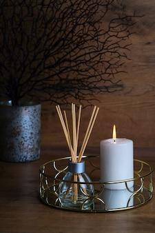 Koncepcja hygge i aromaterapia świece i dyfuzor zapachowy na stole w domu