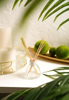 Koncepcja hygge i aromaterapii - świece i dyfuzor zapachowy z zielonymi liśćmi na stole na jasnym tle. wszystko jest ekologiczne i naturalne