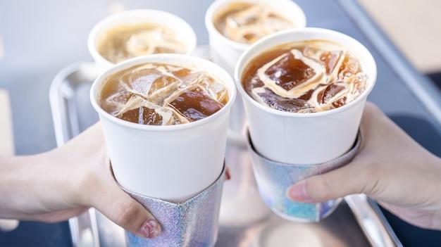 Koncepcja imprezy, dziewczyna z przyjaciółmi trzymają filiżanki kawy i mówią okrzyki szczęśliwemu spotkaniu razem w kawiarni