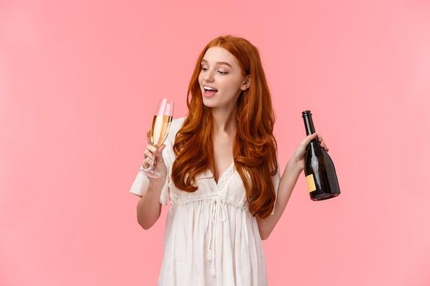 Koncepcja imprezy, kaca i uroczystości. szczęśliwa i wesoła, beztroska, ładna ruda kobieta pije szampana ze szkła, trzyma butelkę, upiła się, zmarnowana stojąc na różowo