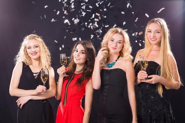 Koncepcja imprezy, święta, uroczystości i życia nocnego - uśmiechnięte koleżanki z kieliszkami szampana w klubie.
