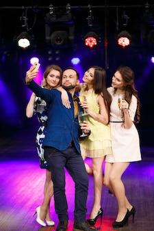 Koncepcja imprezy, wakacji, technologii, życia nocnego i ludzi - uśmiechnięci przyjaciele z kieliszkami szampana i smartfonem biorący selfie w klubie