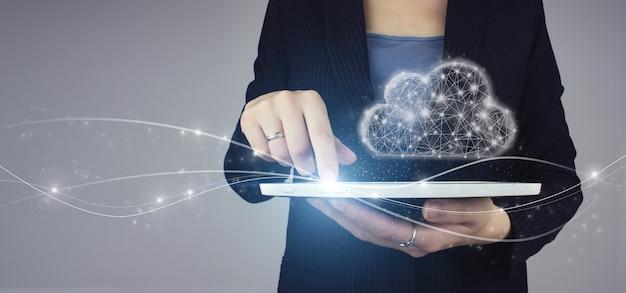 Koncepcja internet technologia cloud computing. biała tabletka w ręku bizneswoman z cyfrowym hologramem cyfrowy znak chmura na szarym tle. sieć komunikacji.