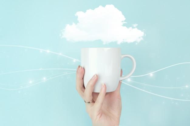 Koncepcja internet technologia cloud computing. dziewczyna ręka trzymać filiżankę kawy rano ze znakiem abstrakcyjna chmura ikona na niebieskim tle.