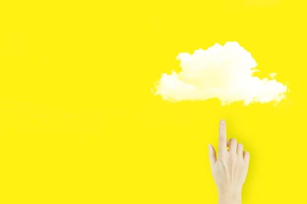Koncepcja internet technologia cloud computing. palec dłoni młodej kobiety wskazując z hologramem streszczenie chmura ikona na żółtym tle. koncepcja przetwarzania w chmurze.