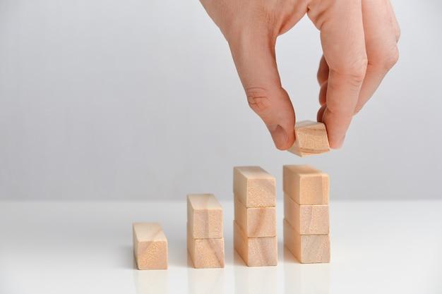 Koncepcja inwestycji biznesowych. ręka trzyma drewniane klocki na białej przestrzeni.