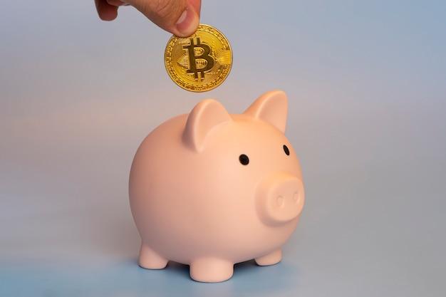 Koncepcja inwestycji w kryptowaluty. męskiej ręki wprowadzenie bitcoin do skarbonki.