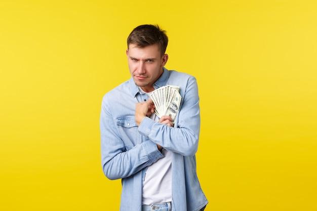 Koncepcja inwestycji, zakupów i finansów. chciwy śmieszny blond facet przytulający pieniądze i patrzący w kamerę, wykazujący intensywne pragnienie zatrzymania gotówki, niechętny udział, stojący na żółtym tle.
